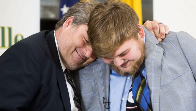Knoxville Catholic offensive lineman Cade Mays, right, hugs his father, Kevin, after signing with Georgia on Wednesday at the school.