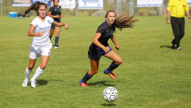 Bloomfield's Natalia Eveland and Piedra Vista's Elizabeth Gephardt chase after the ball during Thursday's girls soccer match at PVHS. Visit daily-times.com to see the latest sports results, photo galleries and video highlights.