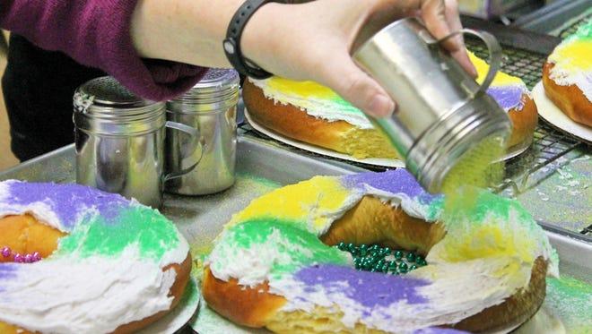 Lilah's Bakery owner Lisa Tike sprinkles Mardi Gras-colored sugar crystals onto freshly baked king cakes.