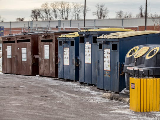 Recycling collection bins sit in a public drop off