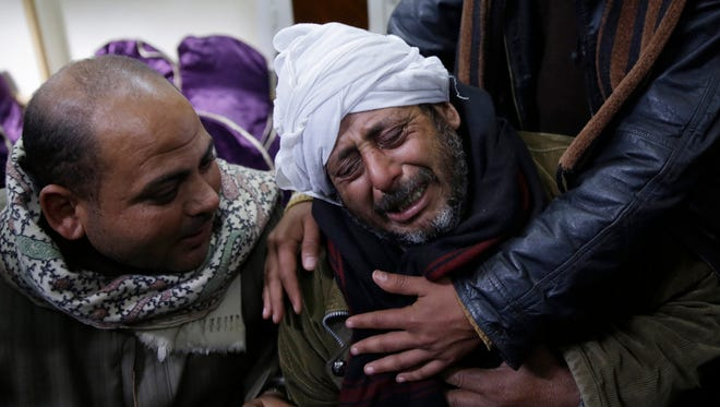 In this Monday, Feb. 16, 2015 file photo, a man is comforted by others as he mourns over Egyptian Coptic Christians who were captured in Libya and killed by militants affiliated with the Islamic State group, outside of the Virgin Mary church in the village of el-Aour, near Minya, 220 kilometers (135 miles) south of Cairo, Egypt.