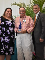 Community Builder Award recipient Bruce Zingman is congratulated by Commissioner Joe Flescher, right, and Keep Indian River Beautiful Executive Director Daisy Packer, left, after surprising him with the award.