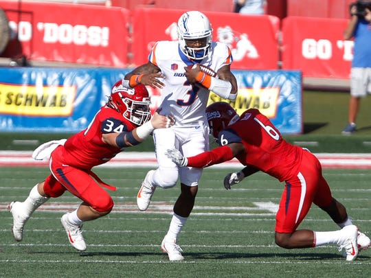 Boise State's quarterback Montell Cozart, center, runs past Fresno State's George Helmuth, left, and Tank Kelly during the first half of an NCAA college football game in Fresno, Calif., Saturday, Nov. 25 2017. (AP Photo/Gary Kazanjian)