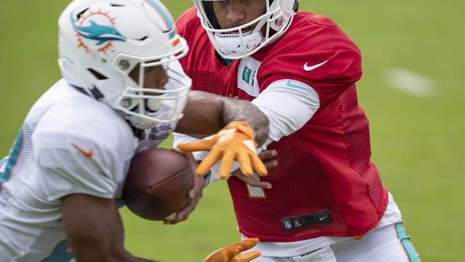 Miami Dolphins quarterback Tua Tagovailoa hands off to Matt Breida at training camp.