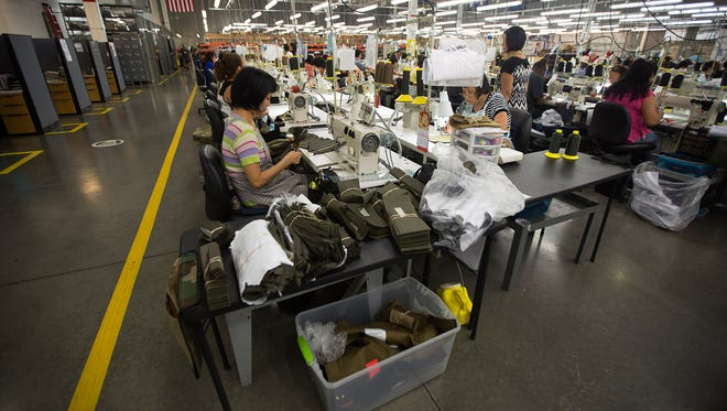 Workers assemble body armor in the sewing area in the Point Blank Body Armor factory in Pompano Beach, Fla.