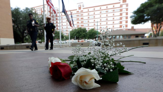 Dallas Police officers walk past roses left at the front doors of the station as part of a makeshift memorial, Friday, July 8, 2016, in Dallas. Five police officers are dead and several injured following a shooting during what began as a peaceful protest in the city the night before.