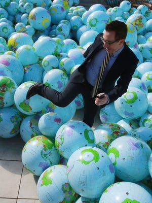 Ben Fyffe, assistant director of the city of El Paso Museums and Cultural Affairs Department, makes his way out of a mountain of beach ball-type globes after having a photo taken Wednesday.