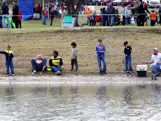 Parents and their children fish for rainbow trout during