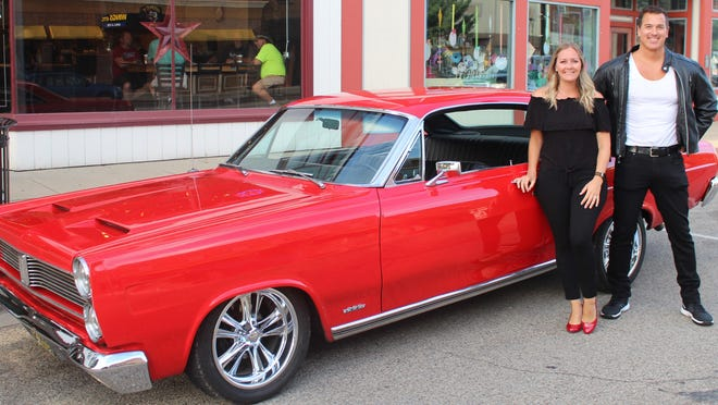 Erin Shoesmith, executive assistant at Sturgis Area Chamber of Commerce, and Ryan Conrod, downtown events coordinator, stand with Joe Myers' 1967 Mercury Comet Caliente in advance of a car show, set for Friday in downtown Sturgis.