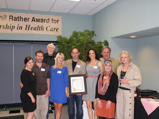 Paul Furman, surrounded by his family, displays one of several proclamations he received as recipient of the 2016 Phil Rather Award for Leadership in Healthcare in the individual Category.
