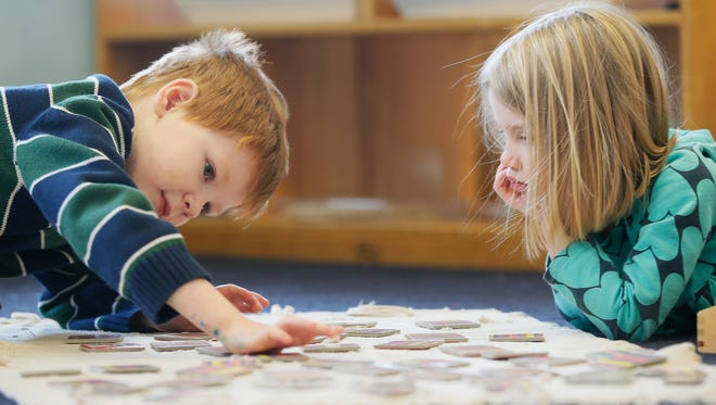 Clara Gerker, 4, right, and Elessar DeHoff, 5, left, complete exercises in the three- to six-year-old Montessori class, Tuesday, Feb. 9, 2016, at Treasure House part of the Children, Inc. network in Covington, Ky.