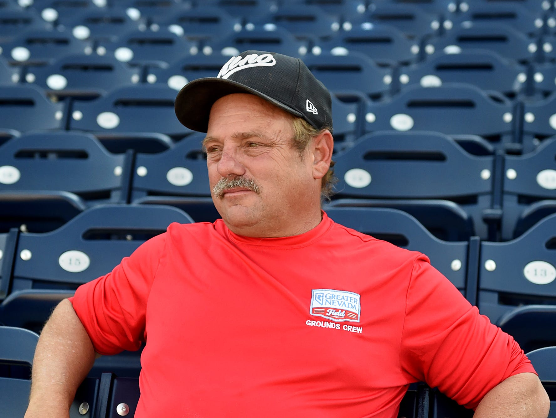 Greater Nevada Field grounds crew member Gray Levy sits in the stadium looking out nto the baseball field on July 26, 2106. Levy has written a book on football.