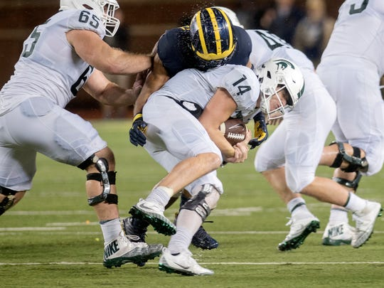 Michigan State quarterback Brian Lewerke is tackled by Michigan's Tyree Kinnel during a run in the fourth quarter on Saturday, Oct. 7, 2017, at Michigan Stadium in Ann Arbor.