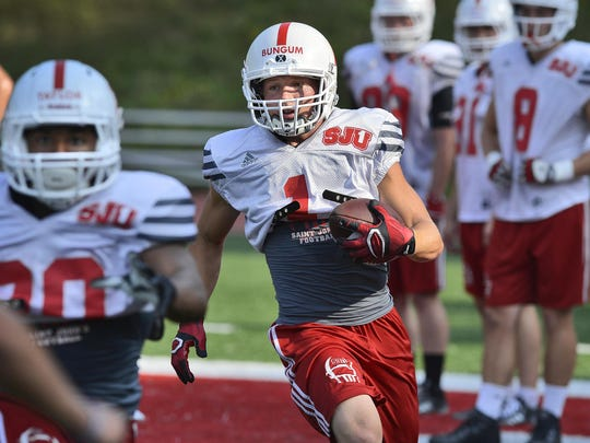 St. John's University senior wideout Josh Bungum (1) carries the ball on a play in practice Wednesday at Clemens Stadium.