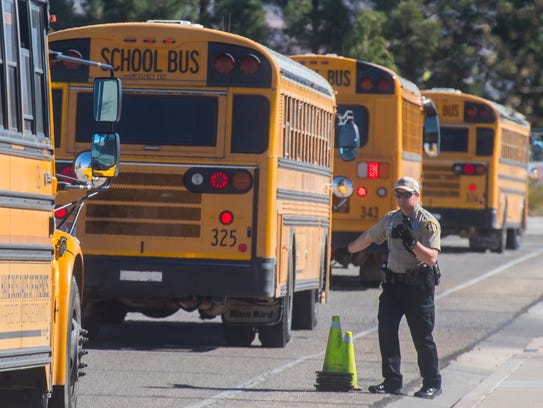 A first responder directs school buses in an evacuation