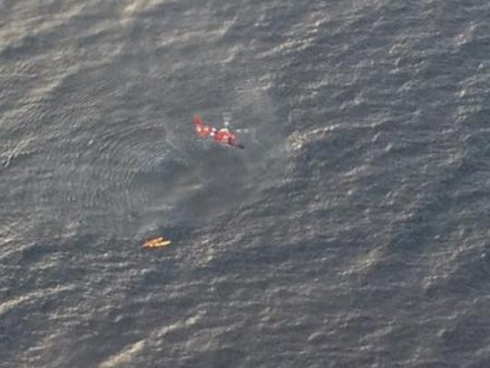 A U.S. Coast Guard Dolphin helicopter from Traverse City, Mich., prepares to rescue three kayakers from Whaleback Shoal in Green Bay early Friday morning. The Coast Guard, the Royal Canadian Air Force and several local agencies assisted in the search and rescue.
