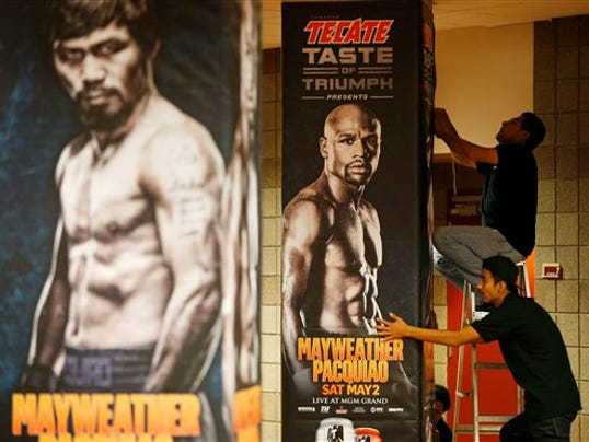 Workers install signs for an upcoming bout at the MGM Grand Garden Arena Monday, April 27, 2015, in Las Vegas. Floyd Mayweather Jr. and Manny Pacquiao are scheduled to fight May 2. (AP Photo/John Locher)