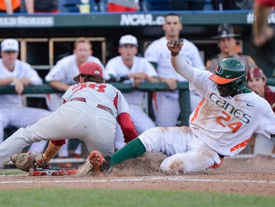 Miami's Jacob Heyward (24) scores against Arkansas pitcher Lance Phillips (38) during the seventh inning of an NCAA College World Series baseball elimination game in Omaha, Neb., Monday, June 15, 2015. (AP Photo/Ted Kirk)