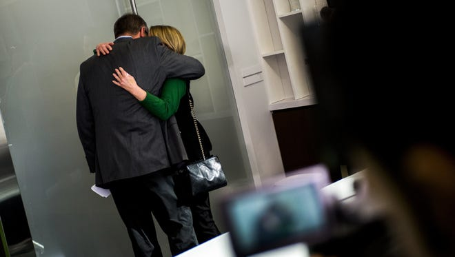 Michigan State athletic director Mark Hollis hugs his wife Nancy after announcing his retirement.