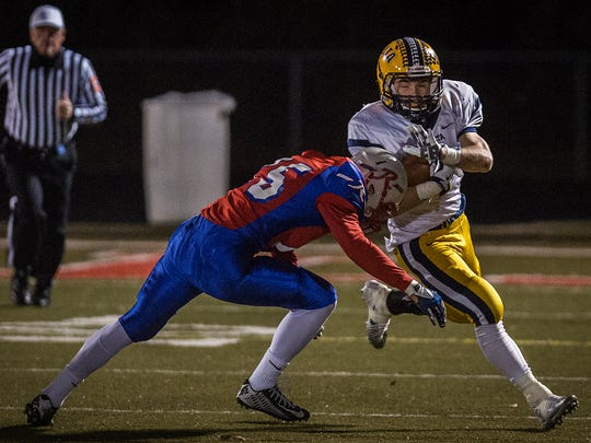 Delta's Zach Mills fights past Roncalli's defense during their regional game at Roncalli High School on Friday, Nov. 13, 2015.