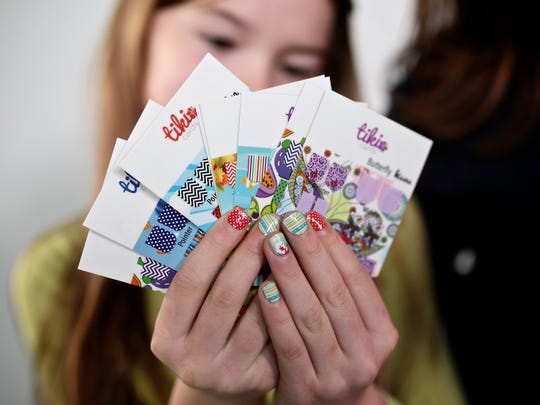 Tess O'Donnell, 9, of Plymouth photographed holding Tiki Cards on Saturday, April 23, 2016 in Detroit, MI. Kelly O'Donnell created the online nail sticker company for kids with her daughters.