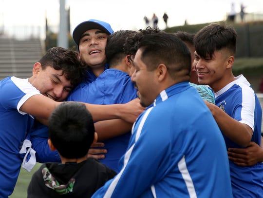Players and staff hug Woodburn head coach Leroy Sanchez,