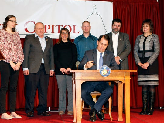 Governor Scott Walker signs an executive order during