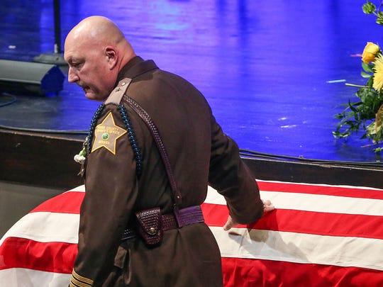 Boone County Sheriff Mike Nielsen touches the casket after speaking at the funeral for Deputy Jacob Pickett, at Connection Pointe Christian Church in Brownsburg, Ind., Friday, March 9, 2018. Pickett was fatally shot the morning of Friday, March 2, while chasing a man fleeing from police. He was a five-year veteran of the department and is survived by his wife Jennifer and two young children.