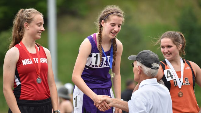 Albany's Kristine Kalthoff shakes hands with meet official Dale Freese after winning the 3,200-meter run May 30 in Collegeville. Erika Swanson of the Northwest Nighthawks (left) took second and Lilly Lee of Ogilvie was third.