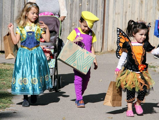 In this file photo, children go trick-or-treating at