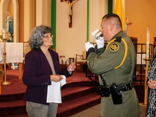 A U.S. Border Patrol Agent drinks sacramental wine