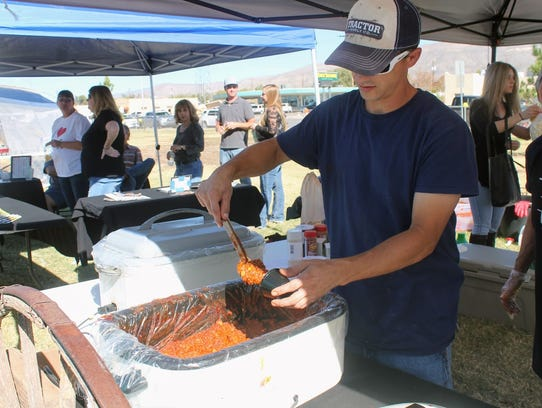 A chili cook-off participant scoops up chili ready