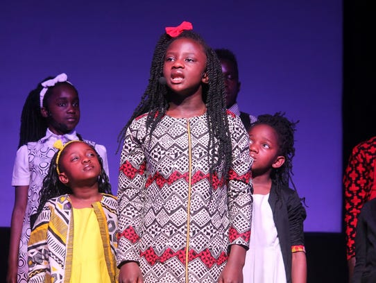 A child sings a song during a free concert at Calvary