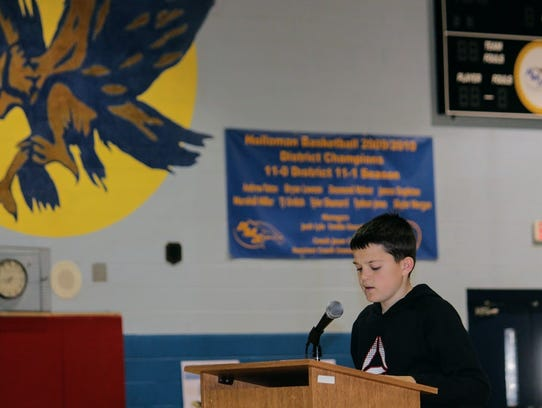 A Holloman Middle School student reads an essay on