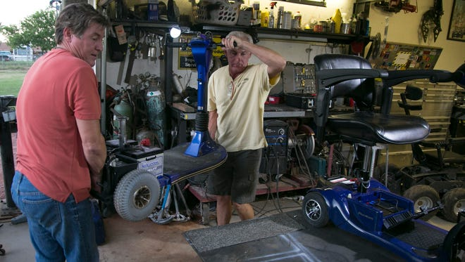 Lance Greathouse (left) and Charlie Vierhout lift a broken motorized scooter onto a workbench so that it can be repaired and upgraded in Greathouse's garage in west Phoenix.