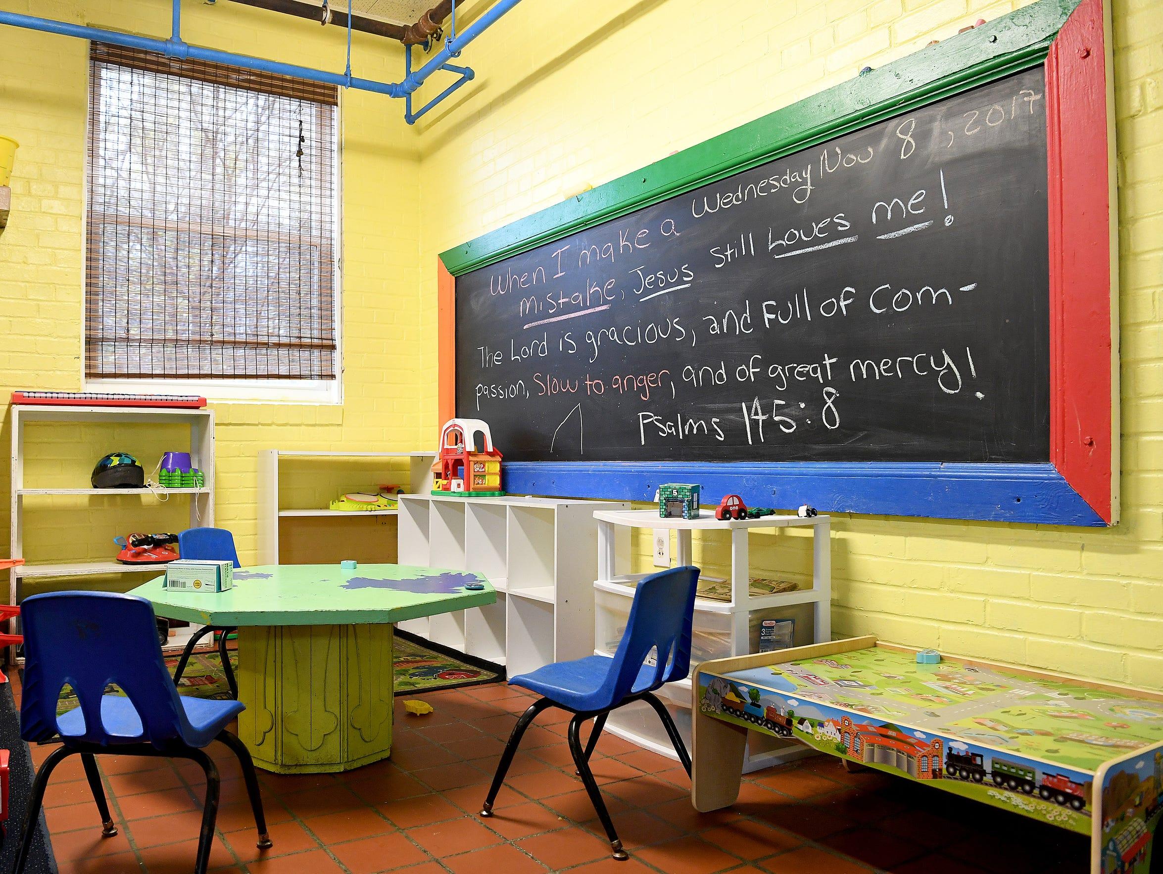 A bible verse is written on the chalkboard in a children's