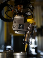 A small robot applies glue to the lens of a missile seeker at Raytheon in Tucson. The lenses can easily be inverted by human engineers, and using the robots helps free up workers from mundane tasks to focus on more complex work that can't be accomplished by machines, officials said.