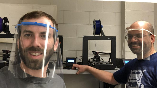 Minisink Valley Middle School technology teachers Rich Budd, left, and Jonathan Clemmons, right, voluntarily make face shields using a district 3D printer.