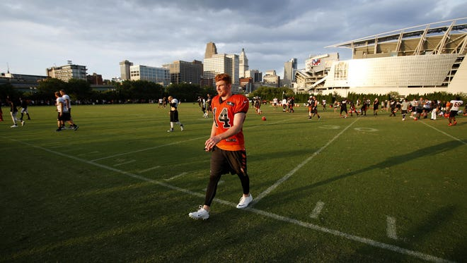 Bengals quarterback Andy Dalton (center) walks over to sign autographs for fans following the team's training camp on Aug. 7, 2015, on the practice fields adjacent to Paul Brown Stadium.