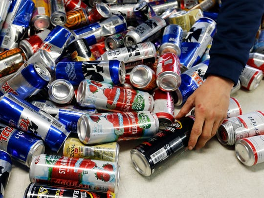 Ben Allen sorts through a table full of cans on Thursday, March 16, 2017, at the Kans R Us redemption center in Perry, Iowa.
