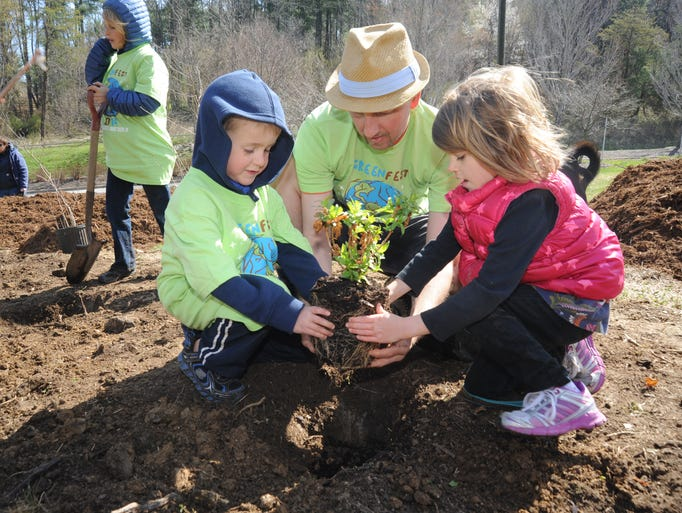 "James ""Buck"" Schall helps his son Jackson, 6, and Ada graham, 5,  plant blueberry bushes in the area of  525 Broadway near the Reed Creek Greenway as part of the school's GreenFest Day of Service Saturday. John Coutlakis 4-5-14"