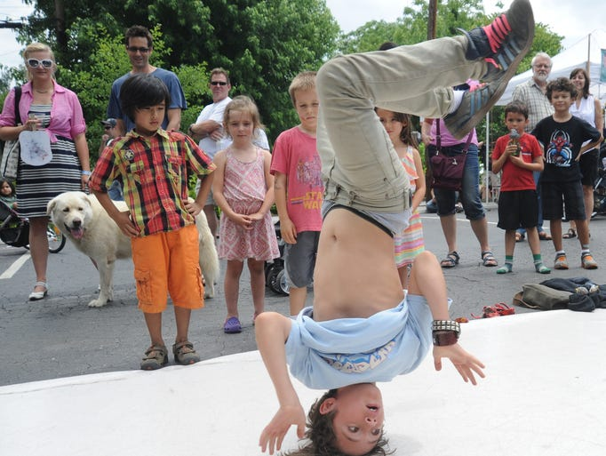 Jerry Vanlandingham, 12,  draws a crowd of onlookers awith his break dancing moves to music by the band Elephant Wrescking Ball during the All Go West Music Festival in West Asheville at 743 Haywood Road Saturday. The festival celebrates  West Asheville's  bustling and unique culture and to highlight local businesses, artists, and non-profits. John Coutlakis 6-7-14