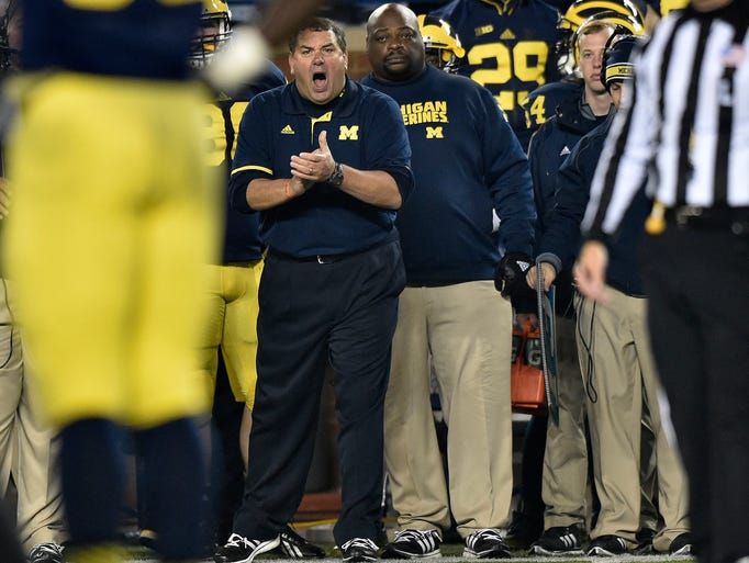 Michigan Wolverines head coach Brady Hoke stands on