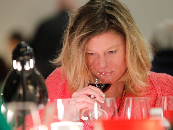 Jennifer Tyndall of Farmington takes in the aromas of a glass of red during the 14th annual Finger Lakes International Wine Competition at the Rochester Plaza in Rochester Sunday afternoon, March 30, 2014.