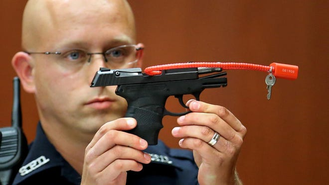 In this June 28, 2013, file photo, Sanford police officer Timothy Smith holds up the gun that was used to kill Trayvon Martin, while testifying in the George Zimmerman trial, in Seminole circuit court in Sanford, Fla. The pistol former neighborhood watch volunteer Zimmerman used in the fatal shooting of Martin was pulled from an online auction minutes afer it opened. (AP Photo/Orlando Sentinel, Joe Burbank)