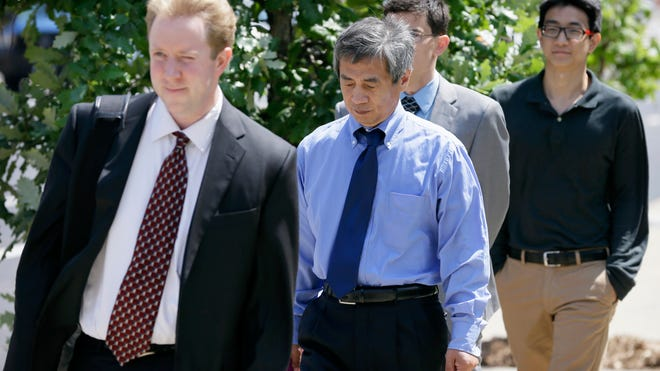 Former Iowa State University scientist Dong-Pyou Han, center, leaves federal court in Des Moines with his attorney Joe Herrold, left, on Tuesday. Han entered not-guilty pleas to four counts of making false statements.