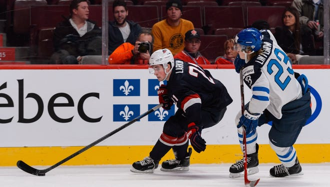 Detroit Red Wings prospect  Dylan Larkin, left, of Team United States tries to carry the puck away from Alex Lintuniemi of Team Finland during the 2015 IIHF World Junior Hockey Championship game at the Bell Centre on December 26, 2014 in Montreal, Quebec, Canada.