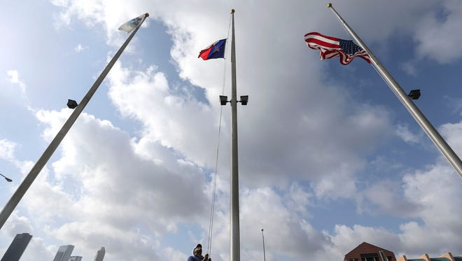 A city of Houston employee lowers the flags in front of the Houston Police Memorial at Memorial Park to half staff,  Friday, July 8, 2016, in Houston, in response to five police officers who were fatally shot during what began as a peaceful protest in Dallas the night before.