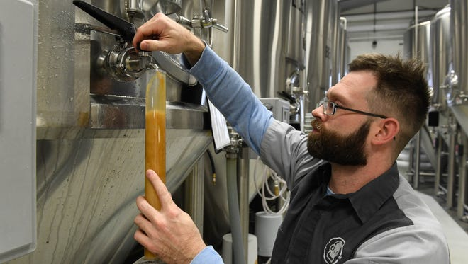 Tin Man Brewing Company operations manager Jason Hoffman taps off a sample of the company's popular Rivet beer at their West Franklin location Saturday, December 17, 2016.