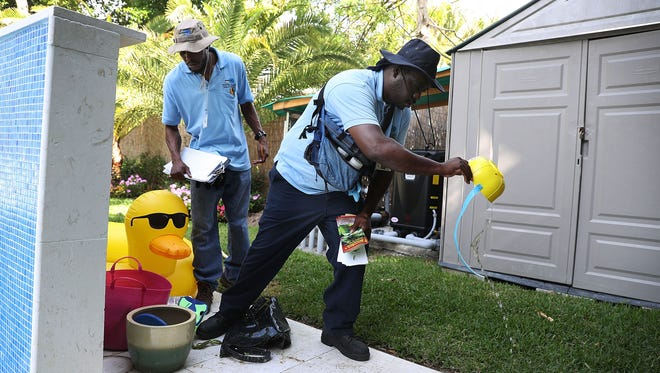 Barrington Sanders and Joseph Blackman with the Miami-Dade County mosquito control department inspect a neighborhood for any mosquitos or areas where they breed as the county works to eradicate mosquitos carrying the Zika virus on April 5, 2017 in Miami Beach, Fla. .